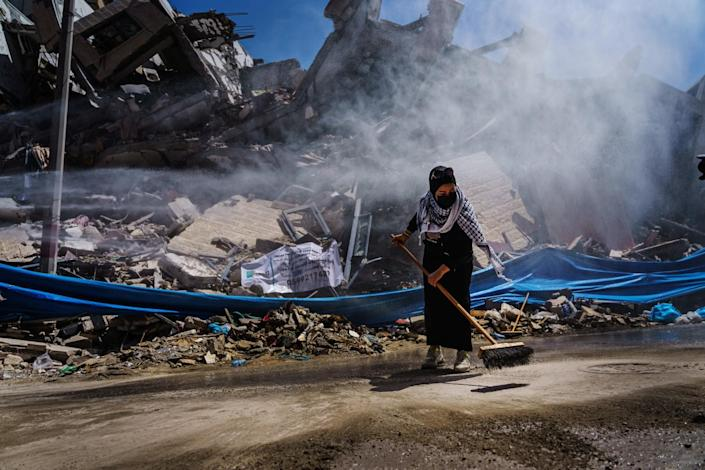 A Palestinian woman helps clean up the rubble and debris of the fallen Hanedi tower.