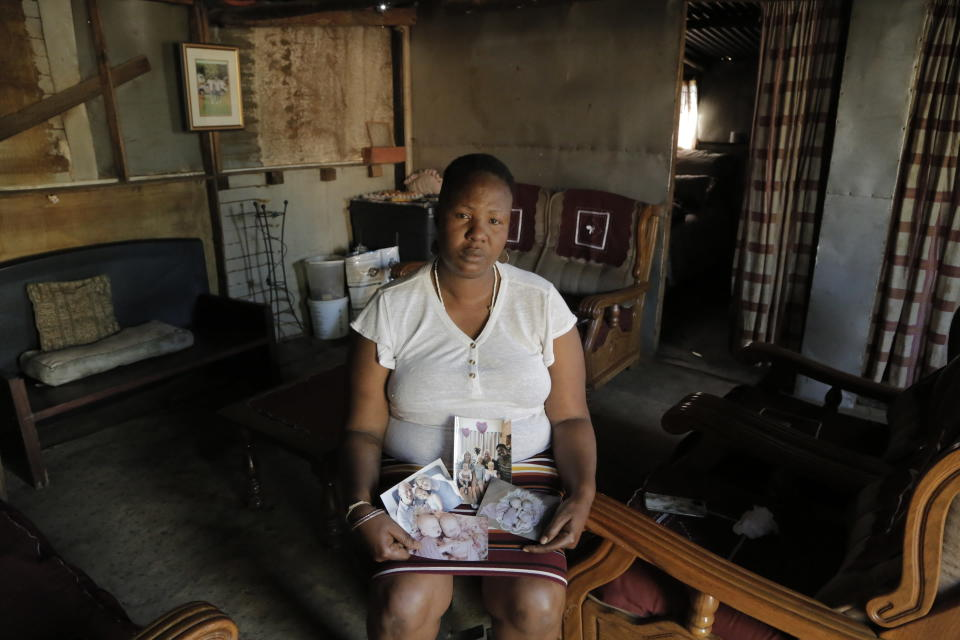 Mandy Sinanyoni, nanny of the three daughters of Graham and Lauren Dickason, holds photographs of the Dickason family in her Pretoria, South Africa home, Friday Sept. 17, 2021. Maya, Karla and Liane Dickason were found dead in the Timaru, New Zealand home they just move into from South Africa. A 40-year-old woman identified by police as Lauren Dickason was charged Friday with killing three young girls in a crime that has shocked New Zealand. (AP Photo/Sebabatso Mosamo)