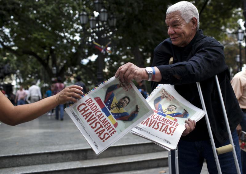 "A man hands out government flyers with a front page image of Venezuela's President Hugo Chavez that reads in Spanish ""Radically Chavists!"" in Caracas, Venezuela, Tuesday Feb. 28, 2012. Doctors successfully extracted a tumor from Chavez's pelvic region and he was stable and recovering Tuesday with family at his side, his vice president announced. (AP Photo/Ariana Cubillos)"