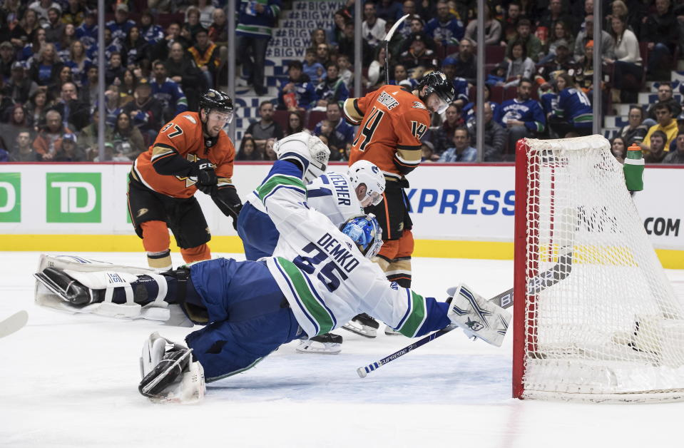 Vancouver Canucks goalie Thatcher Demko (35) dives across the crease as Troy Stecher (51) stops Anaheim Ducks' Nick Ritchie (37) while Adam Henrique (14) watches during the third period of an NHL hockey game Sunday, Feb. 16, 2020, in Vancouver, British Columbia. (Darryl Dyck/The Canadian Press via AP)