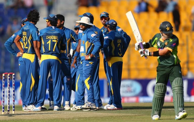 Sri Lankan players jubilate after the dismissal of Pakistani batsman Ahmed Shahzad (L) during the fifth and final One Day International cricket match between Pakistan and Sri Lanka in Abu Dhabi on December 27, 2013.       AFP PHOTO/MARWAN NAAMANI