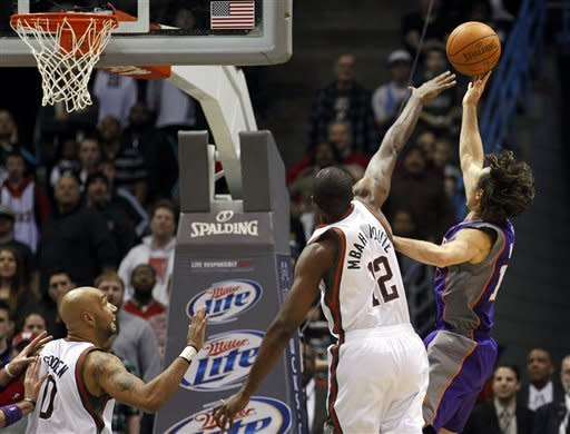 Phoenix Suns' Steve Nash, right, puts up the game-winning shot against Milwaukee Bucks' Luc Richard Mbah a Moute (12) and Drew Gooden, left, during the second half of an NBA basketball game on Tuesday, Feb. 7, 2012, in Milwaukee. The Suns won 107-105. (AP Photo/Jeffrey Phelps)