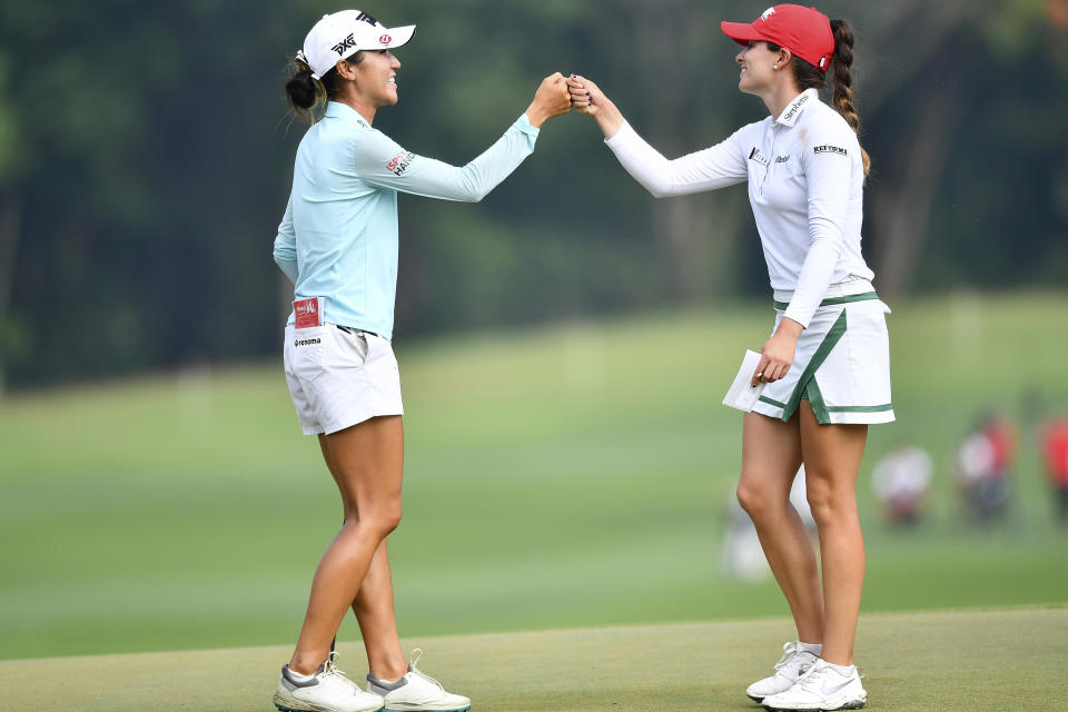 Lydia Ko of New Zealand, left, and Gaby Lopez of Mexico touch their hands after finishing their play on the 18th hole during the final round of the LPGA Honda Thailand golf tournament in Pattaya, southern Thailand, Sunday, May 9, 2021. (AP Photo/Kittinun Rodsupan)