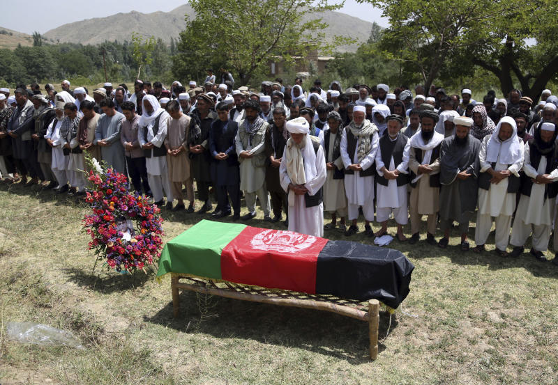 Relatives of Mohammad Akhtar, the driver for Agence France Presse news agency, who was killed in yesterday's suicide attack, offer prayers during his burial ceremony in Guldara district, north of capital Kabul, Afghanistan, Monday, July 23, 2018. An Afghan spokesman said there has been a large explosion near the Kabul airport shortly after the country's controversial first vice president landed on his return from abroad. Gen. Abdul Rashid Dostum and members of his entourage were unharmed in the explosion on Sunday, which took place as his convoy had already left the airport. (AP Photo/Rahmat Gul)