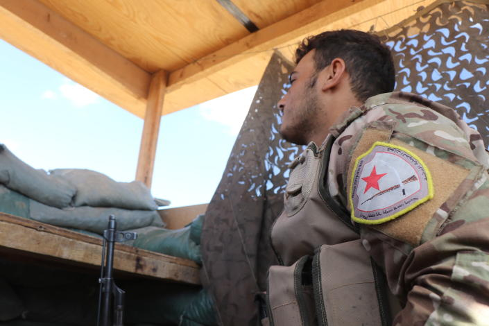 A fighter from the Syrian Democratic Forces, SDF, stands guard inside a post where U.S. troops were based, in Tal Abyad town, at the Syrian-Turkish border, Syria, Monday, Oct. 7, 2019. The SDF, a U.S.-backed Kurdish-led force accused Washington Monday of failing to abide by its commitments by withdrawing from northeast Syria ahead of a Turkish invasion that the Kurds say will overturn five years of achievements in the battle against the Islamic State group. (AP Photo)