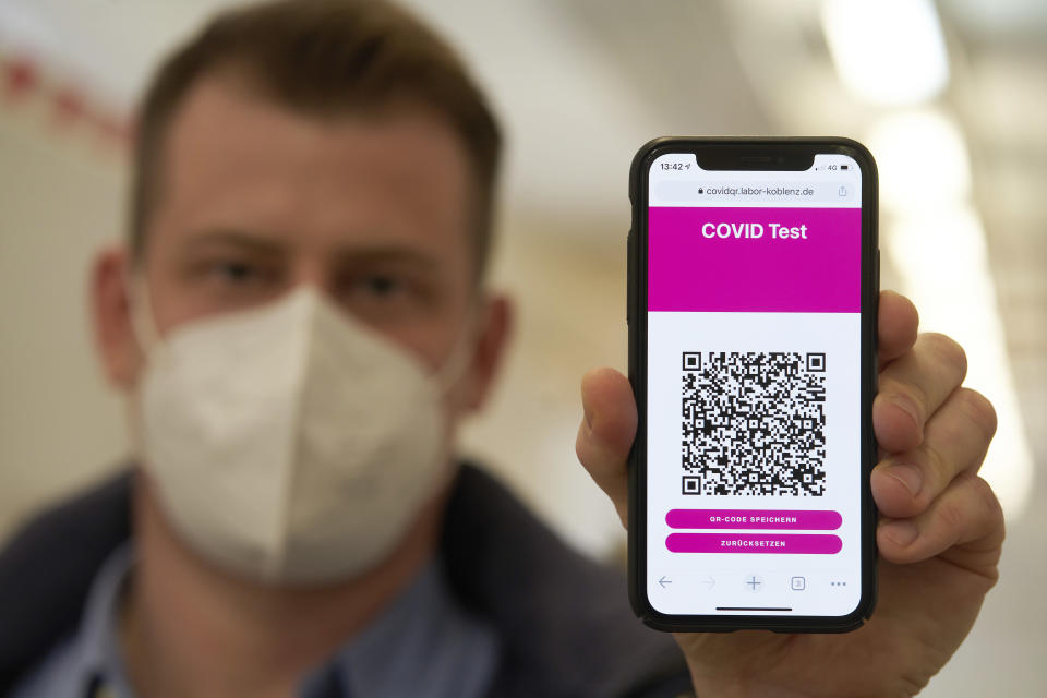 A visitor to the Corona rapid test centre at the Corona Outpatient Clinic in a sports hall shows on his mobile phone the QR code he received with the online appointment confirmation, in Koblenz, Germany, Monday, March 8, 2021. (Thomas Frey/dpa via AP)