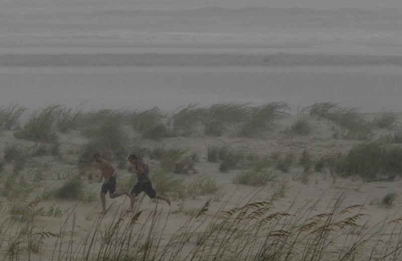 Beachgoers run for shelter as the rain starts pouring down Saturday, Sept. 3, 2011 in Dauphin Island, Ala. As Tropical Storm Lee continues advancing toward the Louisiana coast, the storm dumps sporadic heavy rain along the coasts.  (AP Photo/Kiichiro Sato)