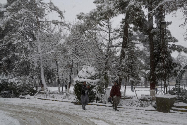 In this Sunday, Jan. 12, 2020, photo, people walk on a road during heavy snow fall in Quetta, capital of Pakistan's southwestern Baluchistan province. Much of the damage was caused in Pakistan's southwestern Baluchistan province where Imran Zarkon, the head of provincial disaster management authority said 14 people were killed in the past 24 hours because of roofs amid winter's unusual snowfall, which also blocked highways and disrupted normal life. (AP Photo/Arshad Butt)