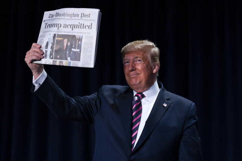"""President Trump holds up a newspaper with the headline that reads """"Trump acquitted"""" during the 68th annual National Prayer Breakfast at the Washington Hilton on Thursday. (AP Photo/ Evan Vucci)"""