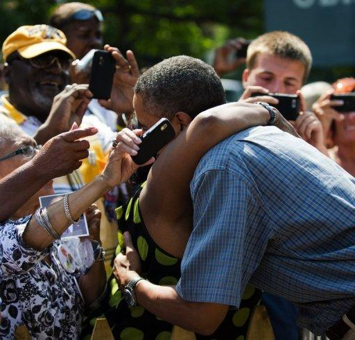 <p>US President Barack Obama is hugged as he arrives for a campaign event at Washington Park in Sandusky, Ohio, July 5. Obama heralded his first re-election campaign bus tour with a new trade blast at China and fresh accusations his White House foe Mitt Romney helped send US jobs abroad.</p>
