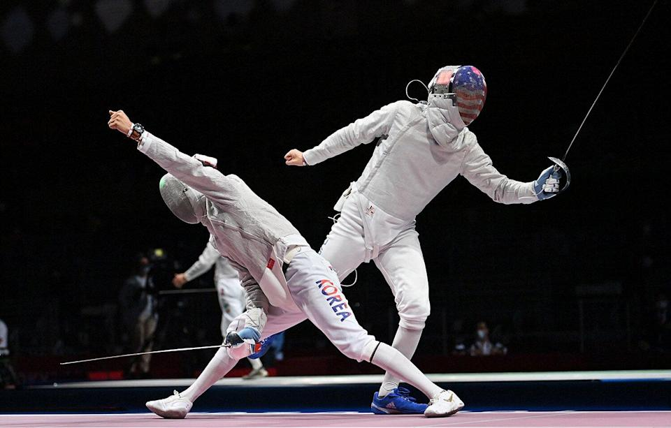 South Korea's Kim Junghwan (L) reacts during the match against USA's Eli Dershwitz in the men's sabre individual qualifying bout during the Tokyo 2020 Olympic Games at the Makuhari Messe Hall in Chiba City, Chiba Prefecture, Japan, on July 24, 2021.