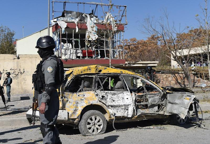 Afghan policemen stand at the site where a suicide bomber targeted a vehicle convoy of lawmakers in Kabul on November 16, 2014 (AFP Photo/Shah Marai)