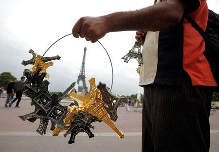 FILE PHOTO: A souvenir vendor sells Eiffel tower models for tourists in front the Eiffel Tower at the Trocadero in Paris, France, July 26, 2011.  REUTERS/Eric Gaillard/File Photo