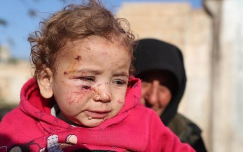 A woman holds an injured girl by last night's Syrian regime bombardment on a makeshift camp in the village of Qah - Credit: AFP