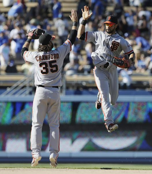 San Francisco Giants shortstop Brandon Crawford, left, and center fielder Angel Pagan celebrate after their win against the Los Angeles Dodgers during a baseball in Los Angeles, Sunday, Sept. 15, 2013. (AP Photo/Chris Carlson)