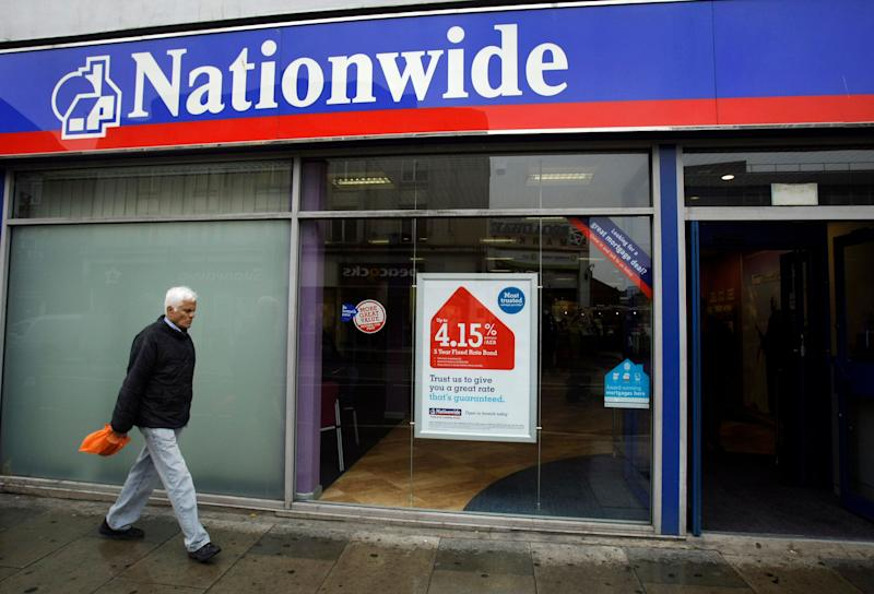 A man walks past a branch of the Nationwide Building Society in Tooting, south London, Wednesday May 27, 2009. The Nationwide Building Society, a major U.K. mortgage lender, reported Wednesday that its full-year profit fell by 67 percent as earnings were hit by write downs for bad loans and a contribution to the government's insurance plan. (AP Photo/Matt Dunham)