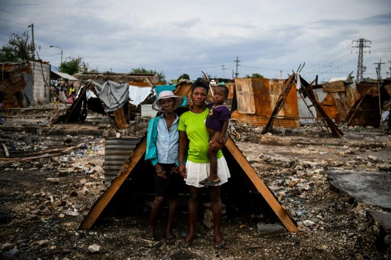 Iris Daniel, 57, Lovely Saint-Pierre, 32, and Evanston Daniel, 5, pose on May 25, 2019, outside a makeshift shelter on the site of their home which was burned during a November 2018 gang war in Port-au-Prince (AFP Photo/CHANDAN KHANNA)