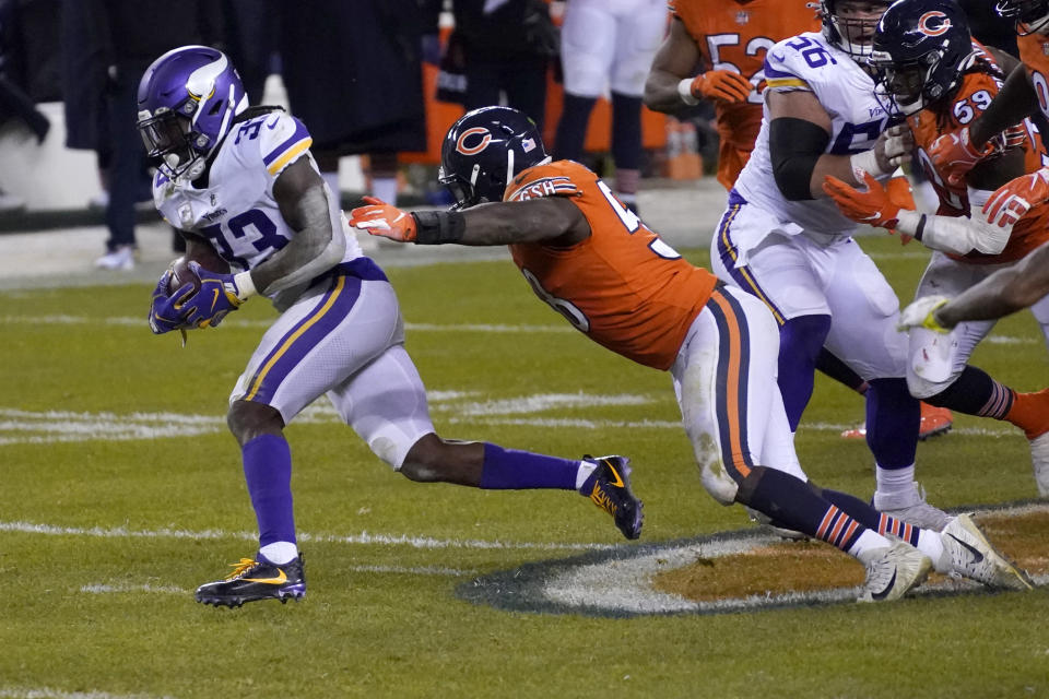 Minnesota Vikings running back Dalvin Cook, left, slips past Chicago Bears linebacker Roquan Smith, right, during the second half of an NFL football game Monday, Nov. 16, 2020, in Chicago. (AP Photo/Charles Rex Arbogast)
