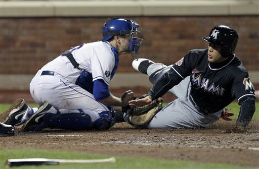 Miami Marlins' Giancarlo Stanton, right, slides safely into home plate past New York Mets catcher Josh Thole on a double hit by Gaby Sanchez during the seventh inning of the baseball game Tuesday, April 24, 2012, at Citi Field in New York. (AP Photo/Seth Wenig)