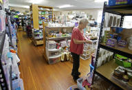 Dorothy Peacock stocks shelves at the grange in Otis, Ore., on Thursday, May. 13, 2020. The makeshift store setup by Cascade Relief Teams takes donations of all kinds and makes them available for free for residents of Otis effected by the Echo Mountain Fire as the small Oregon coast town slowly recovers from the devastating fire that destroyed 293 homes. (AP Photo/Craig Mitchelldyer)