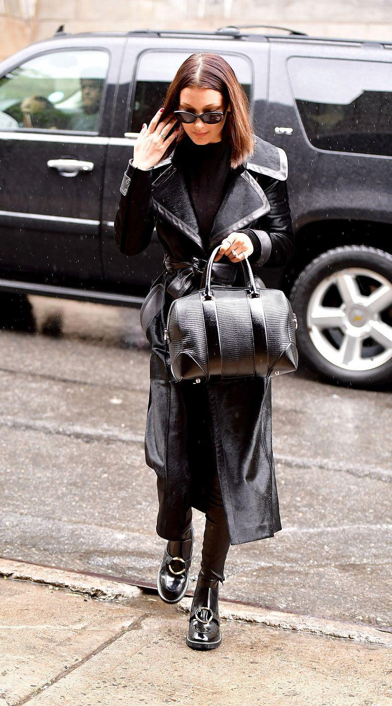 <p>In a black leather-lined trench coat with a Givenchy handbag, patent leather ankle boots and black sunglasses while out in New York City. </p>