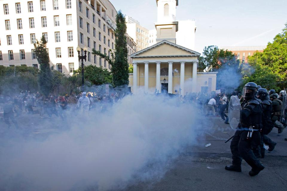 Police officers wearing riot gear push back demonstrators shooting tear gas next to St John's Episcopal Church on Monday. Source: Getty