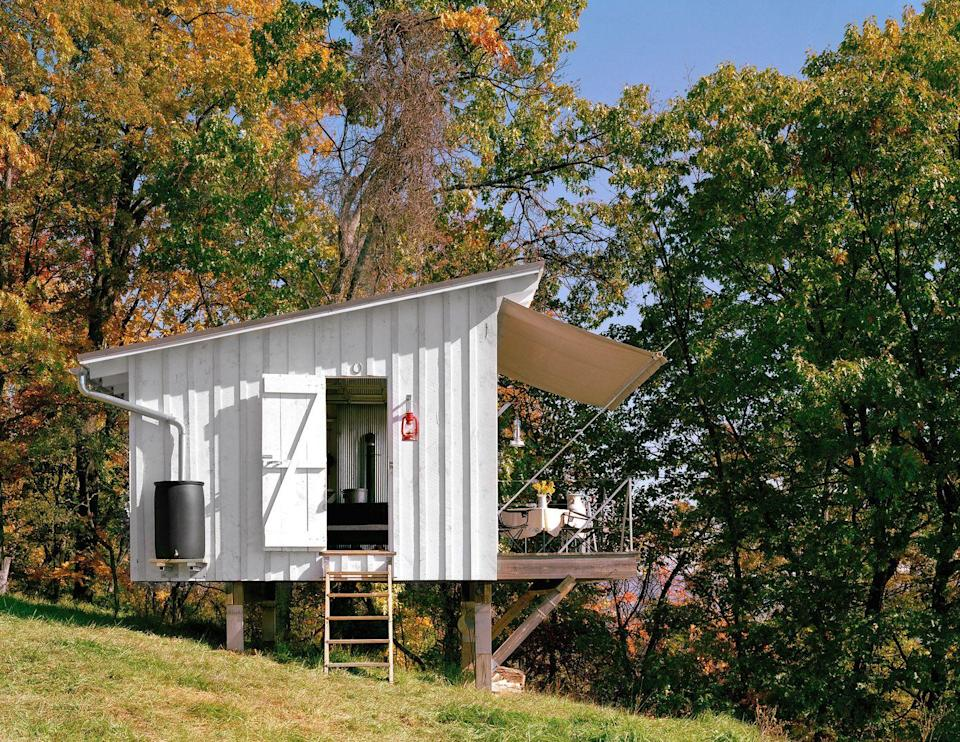 """<p>Designed by <a href=""""http://www.broadhurstarchitects.com/"""" rel=""""nofollow noopener"""" target=""""_blank"""" data-ylk=""""slk:Broadhurst Architects"""" class=""""link rapid-noclick-resp"""">Broadhurst Architects</a> as a weekend retreat for a family from the suburbs of Washington, D.C., The Shack at Hinkle Farm sits on the southern slope of South Fork Mountain in West Virginia. With no electricity, the family relies on oil lamps for light and a small wood stove for heat; rain water is collected from the roof for the outdoor shower. An aluminum and glass garage door opens to a cantilevered wooden deck, where a removable canvas awning offers shade and shelter. </p><p><a class=""""link rapid-noclick-resp"""" href=""""http://tinyhouseswoon.com/the-shack/"""" rel=""""nofollow noopener"""" target=""""_blank"""" data-ylk=""""slk:SEE INSIDE"""">SEE INSIDE</a></p>"""