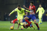 Atletico's Rodrigo Hernandez, right, grabs Barcelona's Lionel Messi by the shirt during a Spanish La Liga soccer match between Atletico Madrid and FC Barcelona at the Metropolitano stadium in Madrid, Saturday, Nov. 24, 2018. (AP Photo/Paul White)