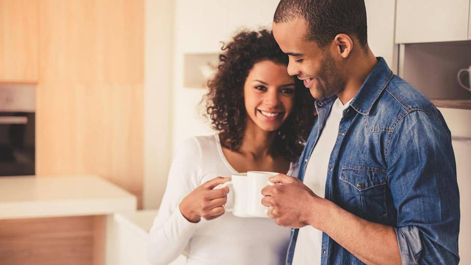 eautiful Afro American couple is drinking coffee, hugging and smiling while resting in kitchen.