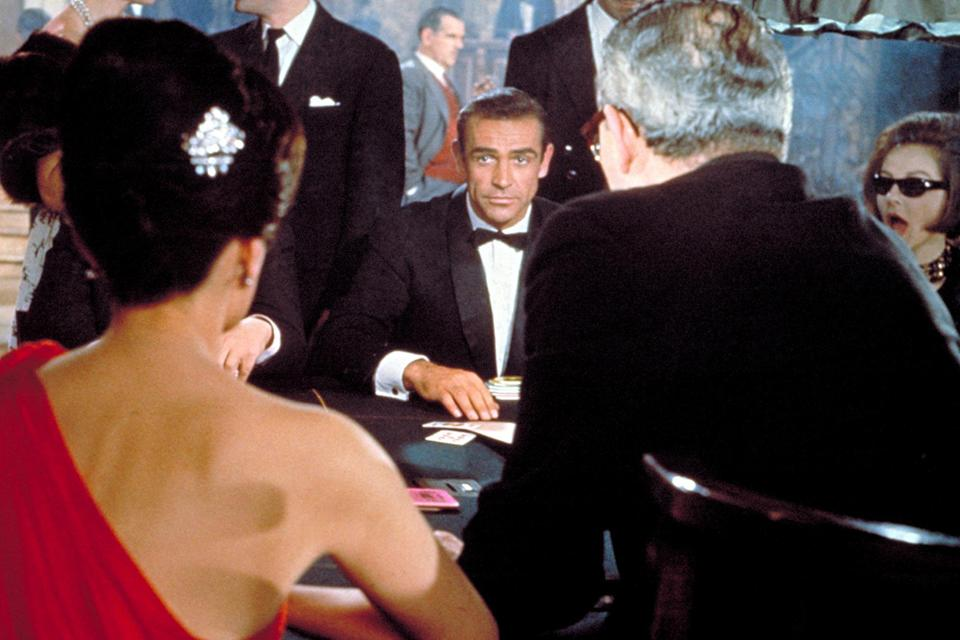 """<p>This isn't just a defining 007 moment, it's the defining 007 moment. And as movie introductions go, it's perfect in every way. Connery, decked out in a natty, slim-fitting tux, is seated at a swank London casino for a high-stakes game of chemin de fer. All eyes are on him — and how could they not be? The sultry Sylvia Trench wants to know who this suave international man of mystery is. Connery's cool-as- the-other-side-of-the-pillow reply is for one the ages: """"Bond, James Bond."""" Cue Monty Norman's slinky, surf-guitar 007 theme. This is the exact moment when a legend was born. As icing, 007 wins the hand... and naturally gets the girl.</p> <p><strong><em>Read more from EW's <a href=""""https://ew.com/25-days-of-bond/"""" rel=""""nofollow noopener"""" target=""""_blank"""" data-ylk=""""slk:25 Days of Bond"""" class=""""link rapid-noclick-resp"""">25 Days of Bond</a>, a celebration of all things 007 ahead of the release of </em>No Time to Die<em>.</em></strong> <strong><em>For even more James Bond, pick up</em> Entertainment Weekly: The Ultimate Guide to James Bond </strong><em><strong><a href=""""https://amzn.to/3iqTVMx"""" rel=""""nofollow noopener"""" target=""""_blank"""" data-ylk=""""slk:here"""" class=""""link rapid-noclick-resp"""">here</a> or wherever magazines are sold.</strong></em></p>"""