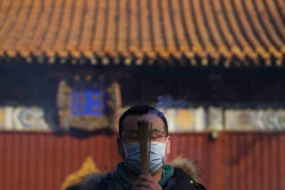A man wearing a face mask to help curb the spread of the coronavirus holds incense offers prayers on the first day of the New Year at Yonghegong Lama Temple in Beijing, Friday, Jan. 1, 2021. President Xi Jinping said in a New Year address that China has made major progress in developing its economy and eradicating rural poverty over the past year despite the coronavirus pandemic. (AP Photo/Andy Wong)