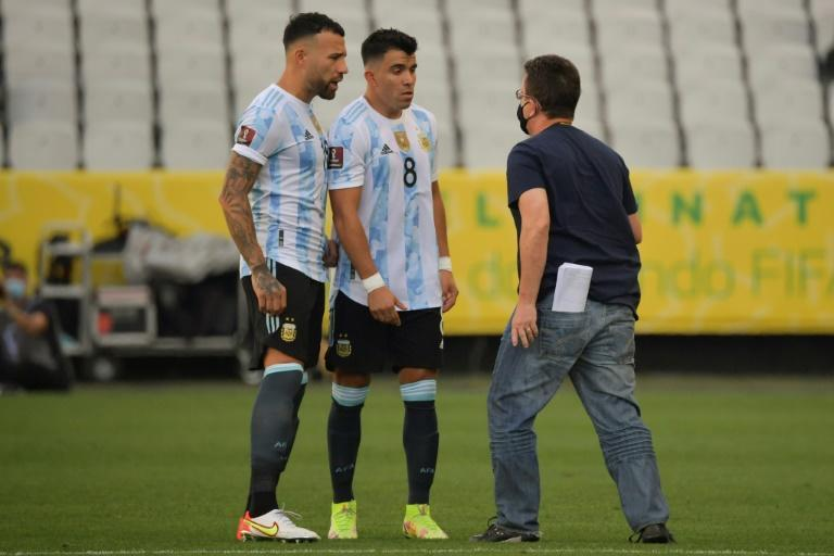 An employee of Brazil's National Health Surveillance Agency (ANVISA) argues with Argentina players Nicolas Otamendi (left) and Marcos Acuna after their World Cup qualifier with Brazil was halted on Sunday (AFP/NELSON ALMEIDA)