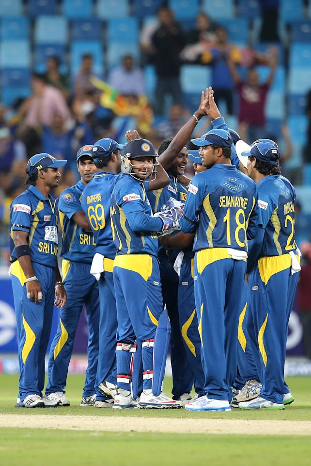 DUBAI, UNITED ARAB EMIRATES - DECEMBER 11:  Players of Sri Lanka celebrate after dismissing Umar Akmal of Pakistan during the first Twenty20 International match between Pakistan and Sri Lanka at Dubai Sports City Cricket Stadium on December 11, 2013 in Dubai, United Arab Emirates.  (Photo by Francois Nel/Getty Images)