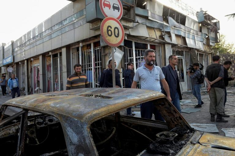 In the town of Barda, men wander by a building and a car hit in the military conflict between Armenia and Azerbaijan over the breakaway region of Nagorno-Karabakh