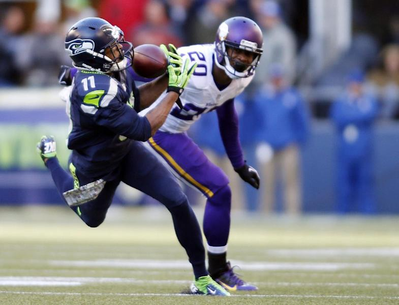 Seattle Seahawks' Percy Harvin (11) catches the ball in front of Minnesota Vikings' Chris Cook in the first half of an NFL football game Sunday, Nov. 17, 2013, in Seattle. (AP Photo/John Froschauer)
