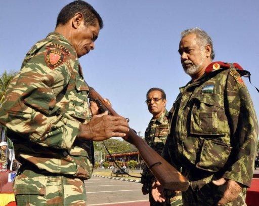 A member of Falintil hands over his rifle to East Timor's prime minister, right