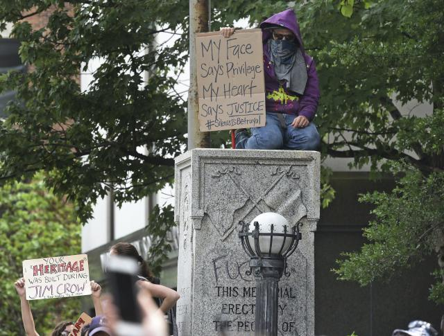 <p>A protester kneels atop the Confederate Memorial to protest in anticipation of a white supremacist march on Friday, Aug. 18, 2017 in Durham, N.C. The sheriff had issued a statement that he was investigating the rumors, but no gathering of white supremacists was apparent by midafternoon. However, officers blocked streets and businesses closed. (Photo: Chuck Liddy/The News & Observer via AP) </p>