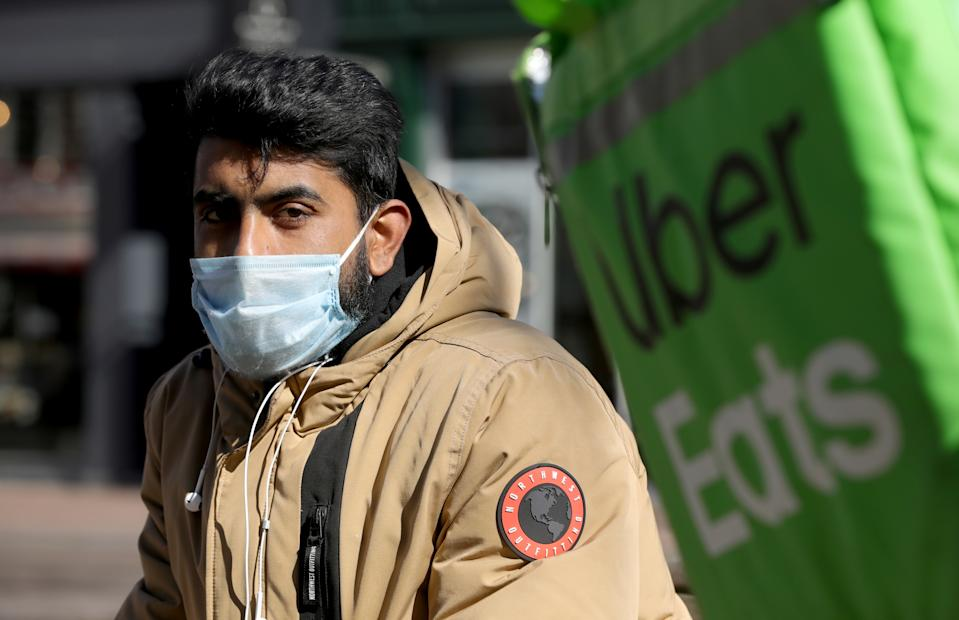 An Uber Eats food delivery courier wearing a protective face mask rides a bicycle as the spread of coronavirus disease (COVID-19) continues in Amsterdam, Netherlands March 25, 2020. REUTERS/Eva Plevier