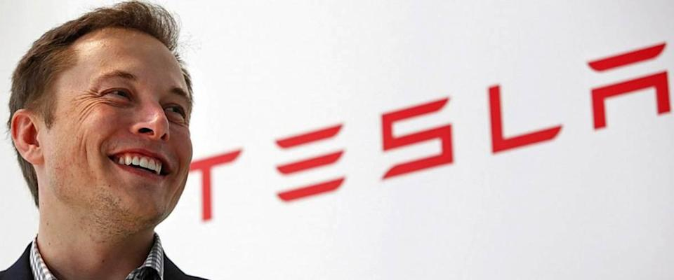 Elon Musk stands next to Tesla logo