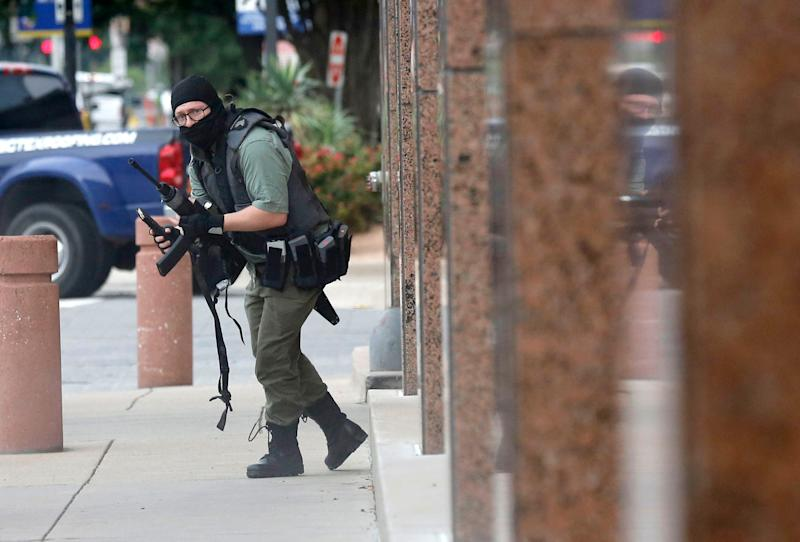 An armed shooter stands near the Earle Cabell Federal Building Monday, June 17, 2019, in downtown Dallas. The shooter fired into the building, and was hit and injured in an exchange of gunfire with federal officers outside the courthouse.