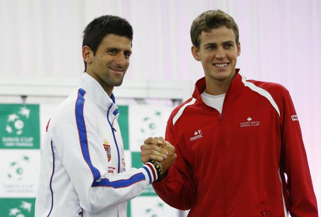 Serbia's Novak Djokovic (L) and Canada's Vasek Pospisil shake hands after the draw for the Davis Cup semi-finals in Belgrade September 12, 2013. Serbia will face Canada in the Davis Cup semi-final match on Friday. REUTERS/Marko Djurica (SERBIA - Tags: SPORT TENNIS)