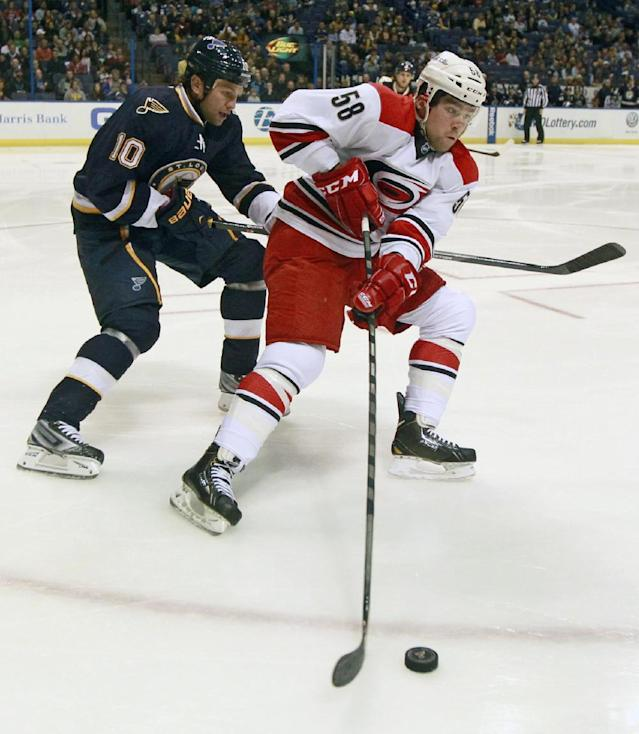 Carolina Hurricanes' Chris Terry, right, controls the puck as St. Louis Blues' Brenden Morrow gives chase during the first period of an NHL hockey game Saturday, Nov. 16, 2013, in St. Louis. (AP Photo/Jeff Roberson)