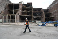 Ron Gobbell, president emeritus of GHP Architecture, walks past damaged buildings Friday, June 25, 2021, in Nashville, Tenn. Six months after a Christmas Day bombing ripped a hole in historic downtown, workers continue to chip away at cleanup efforts so that revitalization can begin. The tediously slow process has meant workers haven't been able to access some of the buildings until recent weeks. (AP Photo/Mark Humphrey)