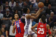 Sacramento Kings guard De'Aaron Fox, center, goes to the basket between Detroit Pistons' John Henson, left, and Derrick Rose, right, during the first half of an NBA basketball game in Sacramento, Calif., Sunday, March 1, 2020. (AP Photo/Rich Pedroncelli)