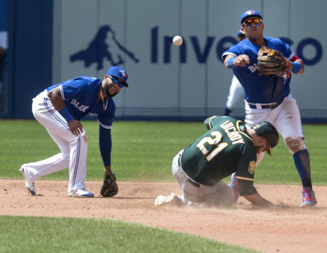 Toronto Blue Jays' Richard Urena and teammate Yangervis Solarte manage to force out Oakland Athletics' Jonathan Lucroy (21) at second base during sixth-inning baseball game action in Toronto, Sunday May 20, 2018. (Fred Thornhill/The Canadian Press via AP)