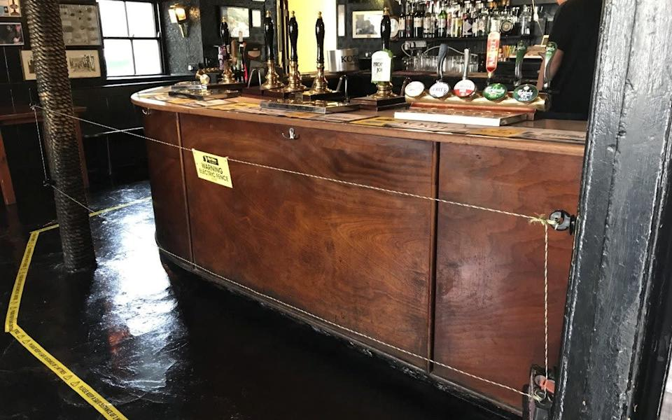 Electric fence to enforce social distancing is pictured in a pub - Tom Lea/Reuters