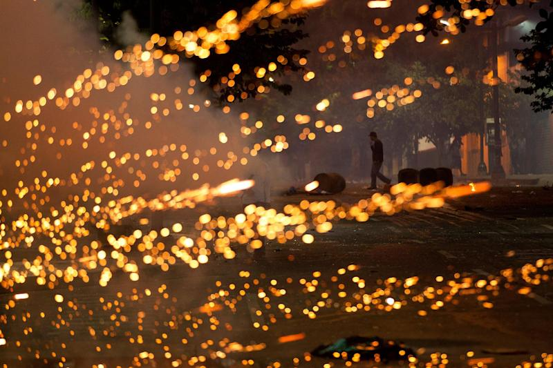 An anti-government protester walks near a burst of lights caused by a fire cracker launched by protesters at Bolivarian National Policemen during clashes in Caracas, Venezuela, Saturday, March 22, 2014. Two more people were reported dead in Venezuela as a result of anti-government protests even as supporters and opponents of President Nicolas Maduro took to the streets on Saturday in new shows of force. (AP Photo/Esteban Felix)