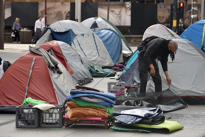 """A homeless man packs up his tent in Martin Place, which has become known as """"Tent City"""", in the central business district of Sydney on August 11, 2017. A homeless tent city in the heart of Sydney was being dismantled on August 11, after political wrangling over who was responsible for the plight of those sleeping rough in the midst of winter sparked the introduction of new laws. / AFP PHOTO / Peter PARKS (Photo credit should read PETER PARKS/AFP via Getty Images)"""