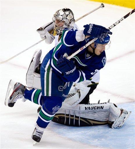 Vancouver Canucks' Dale Weise, right, loses his balance in front of Dallas Stars goalie Kari Lehtonen, of Finland, during the second period of an NHL hockey game, Friday, March 30, 2012, in Vancouver, British Columbia. (AP Photo/The Canadian Press, Darryl Dyck)