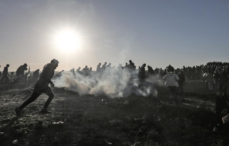 Palestinian protesters ran through tear gas fumes during clashes with Israeli forces following a demonstration along the border with Israel east of Gaza City on January 11